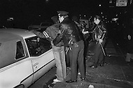 May, 1980. Manhattan, New York City, NY. NYPD police officers keep a watchful eye and batons at the ready while on patrol in Times Square. The area, once a cultural hub, full of theaters, music halls and upscale hotels, declined into a world of sex, drugs and crime and sleazy businesses.<br /> <br /> Manhattan, New York City, NY, Mai, 1980. 23heures: Des policiers patrouillent Times Square, le quartier est dangereux. La proximit&eacute; des sex-shops, les cin&eacute;mas pornographiques, la prostitution et les tripots, furent les facteurs de la d&eacute;t&eacute;rioration du quartier.