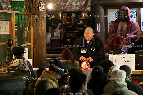 A monk receives a Daruma doll to pray for owner's good luck at the Shorinzan Daruma Temple in Takasaki City, Gunma Prefecture on January 6, 2016, Japan. Every year thousands of people visit the country's most famous Daruma market (Daruma ichi) held at the Shorinzan Daruma Temple on January 6 and 7. Takasaki City, is known as the capital of Daruma dolls and about 80% of Japan's Daruma are produced there. According to the tradition, Daruma dolls are sold without pupils painted on their eyes. People color in one pupil when a wish is made or a goal set, and when the wish comes true or the goal is achieved they fill in the other pupil. At the end of the year, used Daruma dolls are returned to the temple to be burned. (Photo by Rodrigo Reyes Marin/AFLO)