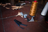Spools of thread and textile scraps are seen on the floor of a small shoe making workshop in San Salvador, El Salvador, 16 November 2016.