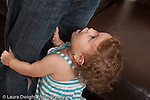 13 month old baby girl at home closeup grabbing father's legs and looking up pleadingly horizontal