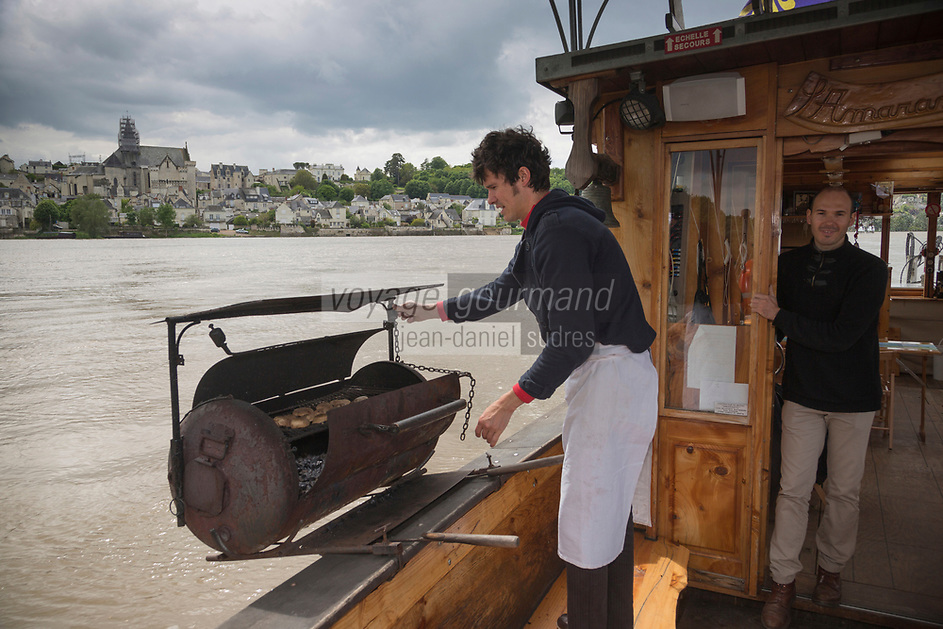 France, Indre-et-Loire (37), Vallée de la Loire classée Patrimoine Mondial de l'UNESCO, Candes-Saint-Martin: Sylvain et Robin Delaporte, déjeuner sur la Loire à bord d'une toue (ancienne barge de commerce à fond plat), sur leur bateau: L'Amarante , préparation et cuisson au barbecue des Galipettes farcies: gros champignons de Paris du Val de Loire avec une farce   // France, Indre et Loire, Loire Valley listed as World Heritage by UNESCO, Candes Saint Martin, labelled Les Plus Beaux Villages de France (The Most Beautiful Villages of France),   Sylvain and Robin Delaporte, lunch on the Loire aboard a toue (old barge trade flat bottom) on their boat: Amarante, preparation and cooking of barbecue Galipettes stuffed: large mushrooms of Paris Loire Valley with a stuffing<br /> <br /> - Auto N: 2013-131   - Auto N: 2013-132