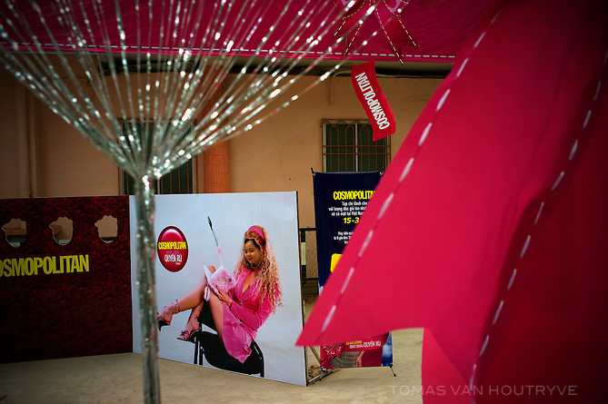 A girl poses behind a cutout of a blond model  as part of a promotional event for Cosmopolitan magazine on International Women's Day at the Young Communist League headquarters in Ho CHi Minh CIty (Saigon), Vietnam on 7 March 2010.