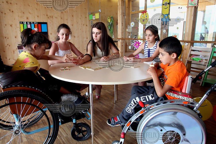 A therapist plays a game with children at Armenian Caritas, 'Emil's Aregak', a supportive and developmental day care centre for children with disabilities and disadvantaged children.