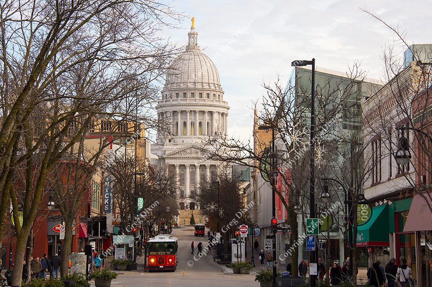 People take the Badger Trolley Bus up State Street in downtown Madison, Wisconsin, with the State Capitol Building in the background, on Saturday, November 28, 2015
