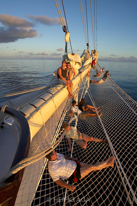 Star Clipper leaving the Virgin Islands at sunset. Courageous passengers enjoy this precious moment from the bow net.