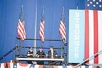 """Police stand behind a stage with campaign signs reading """"Stronger Together"""" after Democratic presidential candidates Hillary Clinton and Bernie Sanders spoke at a campaign rally at Portsmouth High School in Portsmouth, New Hampshire, on Tues., July 12, 2016. At the rally, Sanders officially endorsed Clinton as the Democratic nominee for president."""