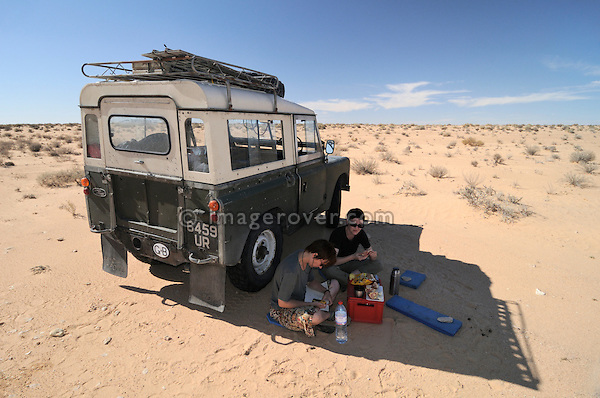 Africa, Tunisia, nr. Douz. Desert travellers Kerstin and Doris having a relaxing rest next to their historic 1962 Land Rover Series 2a.  --- No releases available, but releases may not be needed for certain uses. Automotive trademarks are the property of the trademark holder, authorization may be needed for some uses.  --- Info: Image belongs to a series of photographs taken on a journey to southern Tunisia in North Africa in October 2010. The trip was undertaken by 10 people driving 5 historic Series Land Rover vehicles from the 1960's and 1970's. Most of the journey's time was spent in the Sahara desert, especially in the area around Douz, Tembaine, Ksar Ghilane on the eastern edge of the Grand Erg Oriental.