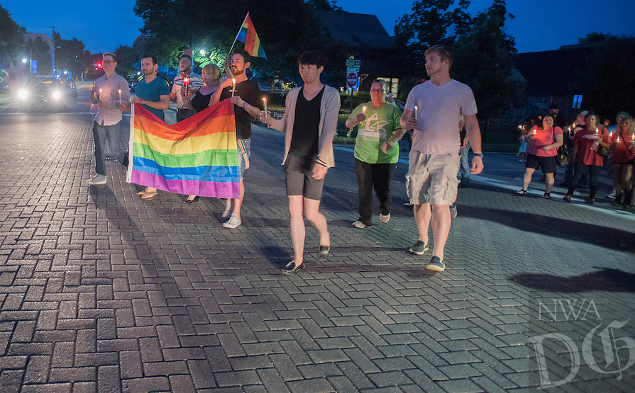 NWA Democrat-Gazette/J.T. WAMPLER Participants march with rainbow flags and candles Sunday June 12, 2016 in Fayetteville after a vigil at St. Paul's Episcopal Church for the victims of the Orlando shooting. Around 500 people attended the vigil and marched down Dickson St.