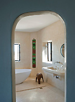 A view through an open doorway to the tadelakt plastered bathroom. A modern stylish, free-standing bath tub stands in the centre of the room and the washbasin is moulded from tadelakt.