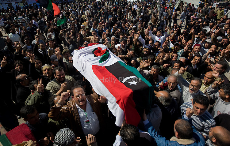 Men carry a coffin away from the main square for burial after the midday prayer in Benghazi, Libya, March 20, 2011. Funerals took place for those killed during fighting between opposition rebels and loyalist forces of Col. Muammar Qaddafi, in Benghazi Libya, March 20, 2011. The main hospital in Benghazi reported around 50 dead fighters and civilians the previous day and at least 35 on Sunday.