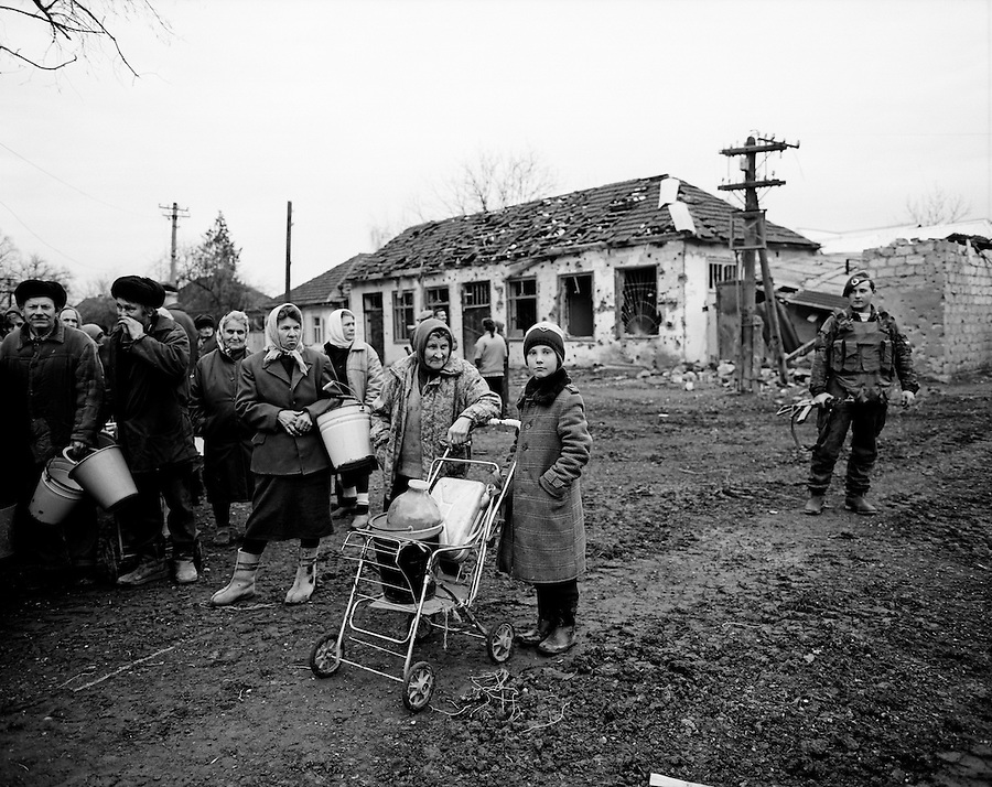 Grozny, Chechnya, March 1995..Civilians queue at dawn for drinking water distributed by Russian soldiers.