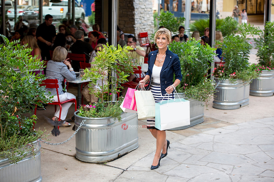 Attractive female shopper walks by an outdoor seating restaurant at an Austin outdoor shopping mall