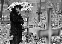 A woman touches a cross marking a grave in the Christian part of Sarajevo's Lion's cemetery on November 13, 1993. Thousands have been killed since the traditionally religiously mixed Bosnian capital was besieged in April 1992.