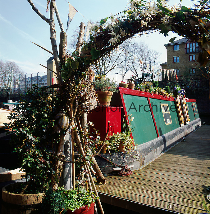 A canal boat in London owned by fashion stylist and artist Emma Freemantle. An arch of twigs and flowers welcomes visitors to the canal boat
