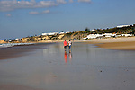 Man and woman walking together on sandy beach at Conil de la Frontera, Cadiz Province, Spain