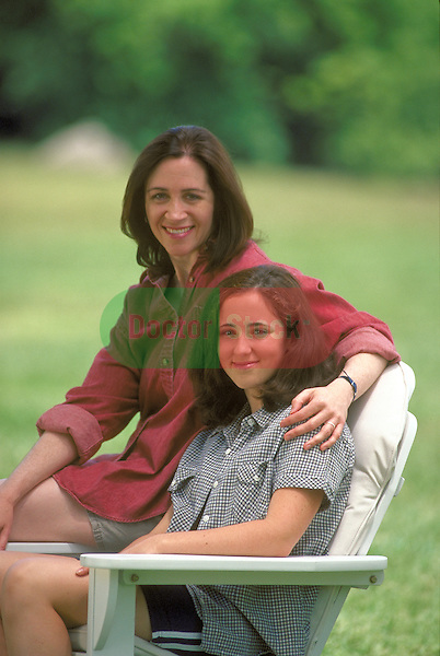 portrait of mother sitting with teenage girl in adirondack chair in park