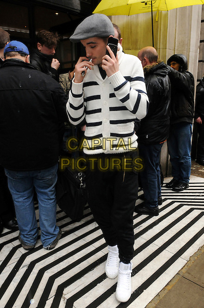THE WANTED - Tom Parker.Arriving at BBC Radio 2, London, England..March 18th, 2011.band group full length jeans denim white hi high top hitop trainers sneakers shoes black striped stripes cardigan grey gray cap hat smoking cigarette profile talking on mobile phone.CAP/IA.©Ian Allis/Capital Pictures.