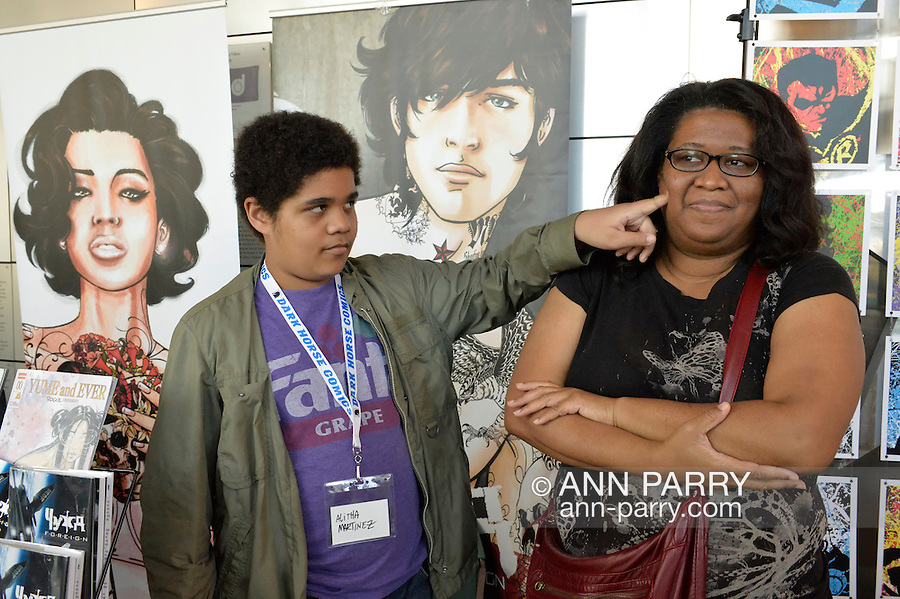 Garden City, New York, U.S. - June 14, 2014 - At right, ALITHA MARTINEZ, an illustrator of  superhero comics such as Black Panther, Iron Man, Spider-Girl, and her own title, Yume and Ever, is one of the comic book illustrators at Eternal Con, the annual Pop Culture Expo, held at the Cradle of Aviation Museum on Long Island.