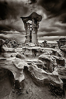 A black and white image of a hoodoo with it's support column eroded clear through in places stands in a remote section of Ah Shi Sle Pah Wash in New Mexico's San Juan Basin.