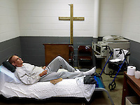 A sick inmate lies on a bed in the prison Chapel, which also serves as the facility's sick bay, in Putnam County Jail in Eatonton.
