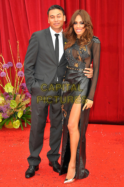 RICKY NORWOOD & JADE EWEN .Attending the British Soap Awards 2011, .Granada Television Studios, Quay Street, Manchester, England, UK, .March 14th 2011..arrivals full length couple thigh leg long sleeve maxi dress slit split mesh sheer see thru through sugababes  grey gray suit black tie hands in pockets .CAP/CAS.©Bob Cass/Capital Pictures.