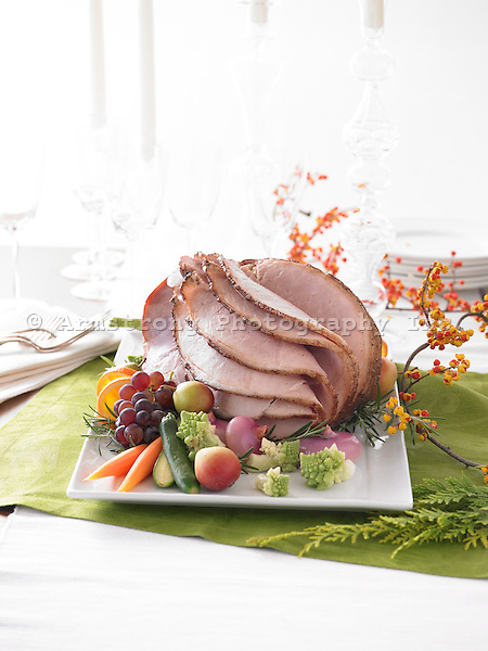 A whole glazed roast ham, sliced, and garnished with fruit and vegetables including cucumber, cauliflower, pears, grapes, carrots, red onion, oranges, and rosemary.