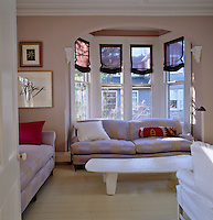 A wooden African bed painted white has been turned into a coffee table and a comfortable sofa sits in the bay window of the family room