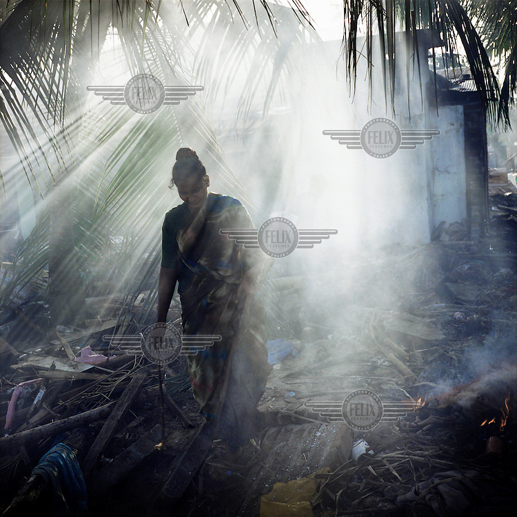 A woman walks among the ruins and detritus of houses destroyed by the 2004 tsunami.