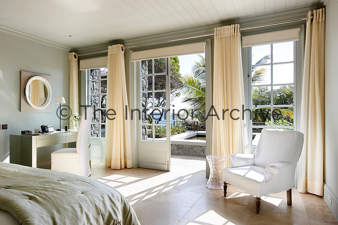A spacious pale green bedroom with a stone tiled floor and french doors, which give access to a terrace. The room has floor to ceiling cream curtains and a  dressing table and chair in the corners.