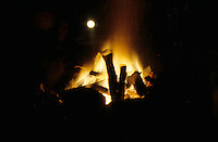 Blurred faces around a campfire.