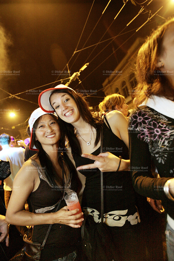 Switzerland. Canton Neuchâtel. Neuchâtel. Grape Harvest Festival. Two young women ( a white and an asiatic). A glass of cranberry juice mixed with vodka. Victory sign with two fingers. Night life. © 2006 Didier Ruef