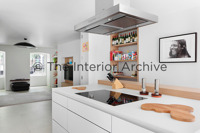 A stainless steel extractor fan above a ceramic hob built into a kitchen unit. The kitchen is in an open plan room that has an informal family area with television.