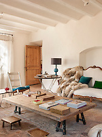 A large piece of wood has been placed on a pair of low trestles to create an oversized coffee table in the living room