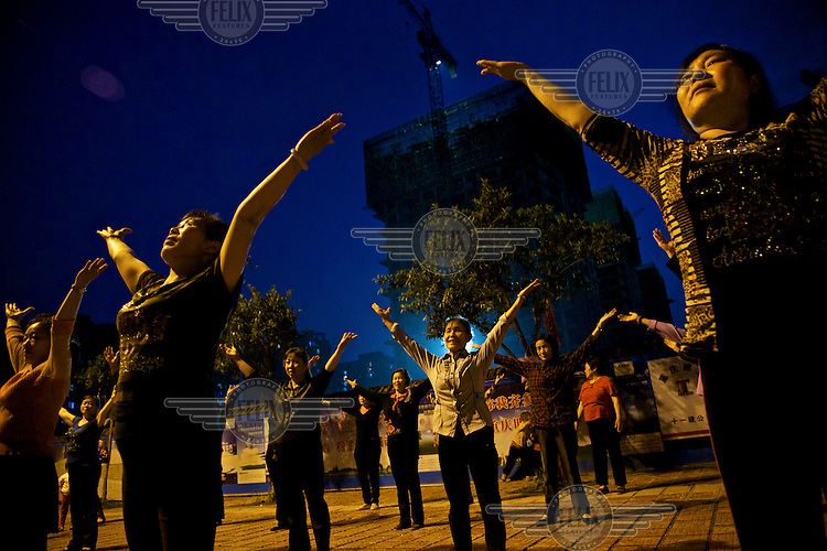 Pensioners dance underneath a new building at a relocation housing project in the southwestern Chinese megapolis of Chongqing. They were all moved from their farmland and resettled nearby in this purpose-built estate. Some bemoan the poor relocation compensation but others are happy to enjoy a social life away from the burden of farming. The Chinese government plans to move 250 million rural residents into urban areas over the coming dozen years though it is unclear whether people want to move and where the money for this project will come from. Further urbanisation is meant to drive up consumption to counterbalance an export orientated economy and end subsistence farming but the drive to get people off the land is causing tens of thousands of protests each year. /Felix Features