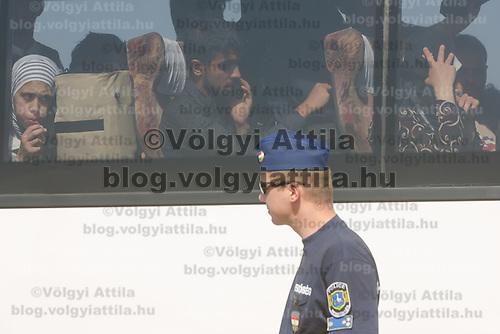 Police officer watches migrants sitting on a bus after crossing the border between Serbia and Hungary before the last opening is closed near Roszke (about 174 km South of capital city Budapest), Hungary on September 14, 2015. ATTILA VOLGYI