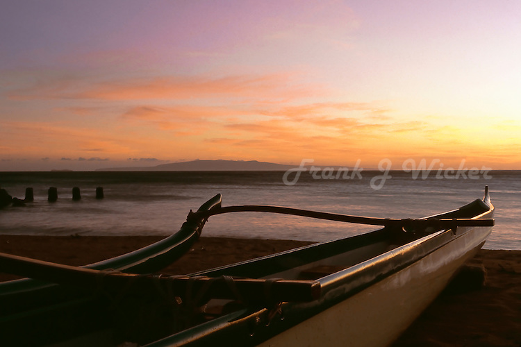 Outrigger canoe on the beach at sunset