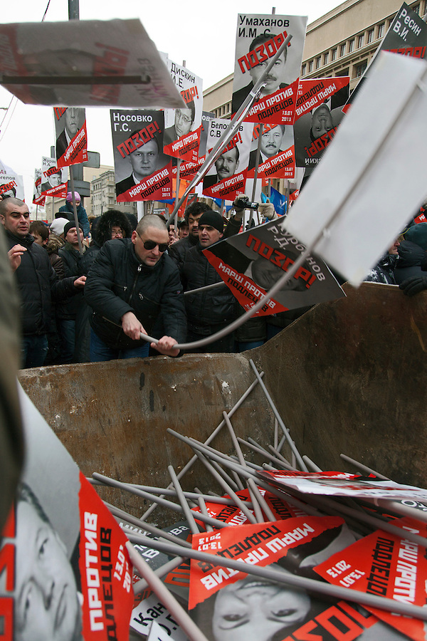 "Moscow, Russia, 13/01/2013..Opposition leader Sergei Udaltsov smashes portraits of Russian politicians into a skip marked ""for garbage"". Thousands of opposition protesters carried posters of President Vladimir Putin and members of the Russian parliament with the word ?Shame? written in red at a protest called the March Against The Scoundrels. The protest was against the new law banning the adoption of Russian children by Americans, widely seen as a response to the recently passed USA Magnitsky Act."