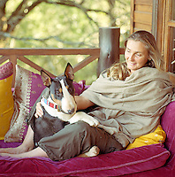 Portrait of jewellery designer Anna Trzebinski and her bull terrier on a sofa on the terrace of her Kenyan home