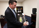Freshman Sen. Ben Kieckhefer, R-Reno, unpacks a Reno Aces photo while setting up his office at the Legislature in Carson City, Nev., on Thursday, Jan. 6, 2011..Photo by Cathleen Allison