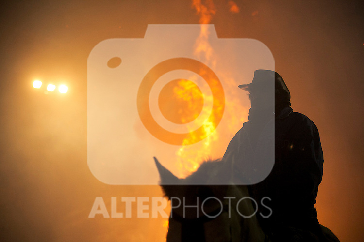 SAN BARTOLOME DE PINARES, SPAIN - JANUARY 16: A man stands with his horse in front of a bonfire on January 16, 2013 in San Bartolome de Pinares, Spain. In honor of San Anton, the patron saint of animals, horses are riden through the bonfires on the night before the official day of honoring animals in Spain. Victor J. Blanco / Alterphotos