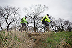 Pix: Shaun Flannery/shaunflanneryphotography.com<br /> <br /> COPYRIGHT PICTURE>>SHAUN FLANNERY>01302-570814>>07778315553>><br /> <br /> 23rd February 2014.<br /> Two Mountain bikers cross a small bridge over a ditch whilst cycling across a field.