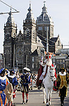 AMSTERDAM - NETHERLANDS - 14 NOVEMBER 2004 -- Arrival of Saint Nicholas to Amsterdam with his helpers Zwarte Pieten (black Peters). -- Sinterklaas, as Saint Nicholas is called in Dutch, riding on his white horse through Amsterdam during his parade. The Church of St. Nicholas in the background. -- PHOTO:  EUP-IMAGES / JUHA ROININEN