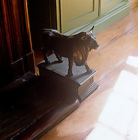 One of a pair of antique bronze bulls stands on either side of a library fireplace creating an interesting focal point