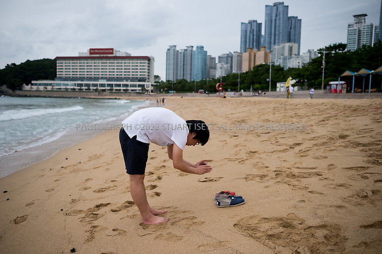 9/3/2013--Busan, South Korea<br /> <br /> A visitor on Haeundae Beach in Busan (Pusan) photographs his and his girlfriend's shoes.<br /> <br /> Photograph by Stuart Isett<br /> &copy;2013 Stuart Isett. All rights reserved.