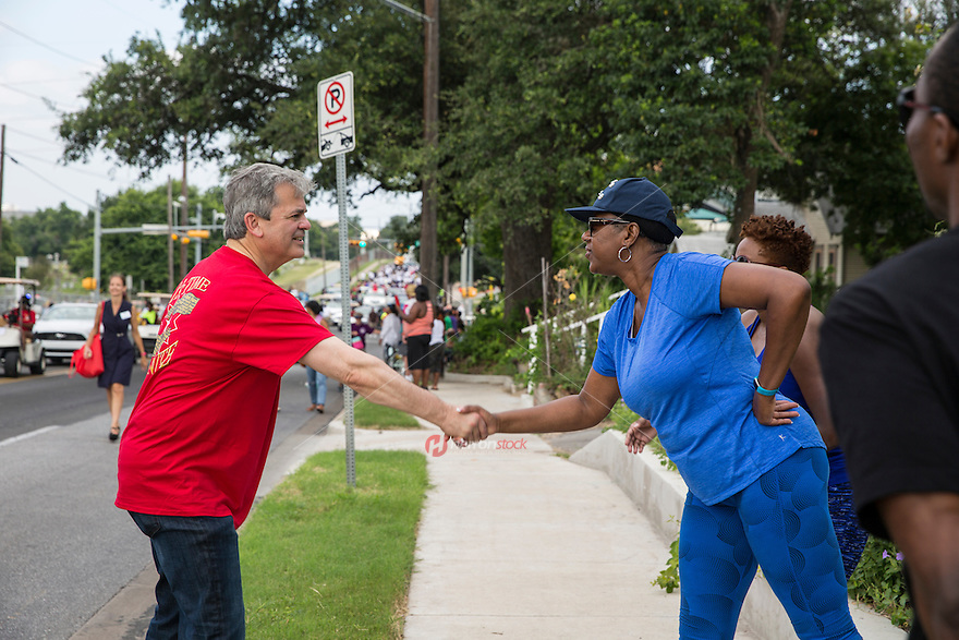 AUSTIN, TEXAS - Austin Mayor, Steve Adler shakes the hand of a parade attendee during the 2016 Central Texas Juneteenth Celebration Parade on Sat. June 18, 2016. <br />