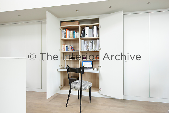 A clever space-saving home-office area is concealed behind the doors of a built-in wall unit. The unit houses shelving space for books, files and a laptop computer. A stylish black chair is placed before a pull-out desk shelf.