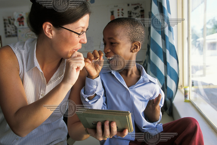 A foreign aid speech therapist, helping a little boy with disabilities with his speech.