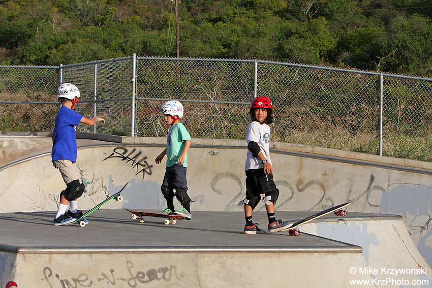 Young boys skateboarding at the Banzai Skate Park, North Shore, Oahu, Hawaii
