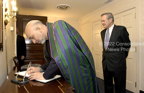 Washington, DC - June 14, 2004 -- President Hamid Karzai of Afghanistan (left) signs the guest book at the Pentagon in Washington, D.C. on June 14, 2004 as United States Secretary of Defense Donald H. Rumsfeld (right) looks on.  The two men will hold talks to discuss a range of security issues peculiar to the Afghan region.  .Credit: Robert D. Ward / DoD via CNP