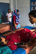 57 year old Usha Srivastava (right) records the blood pressure of a young pregnant woman, 25 year old Mehrul Nisha in the Public Health Centre in Adapur village of Raxaul district of Bihar.